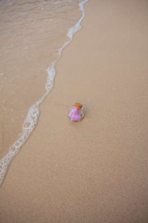 A bottle with a heart Pillow inside is buried on the beach. photo