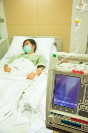 medical technical equipment: An intravenous IV drip infusion pump next to a patients bed in a hospital room with selective focus on the foreground.