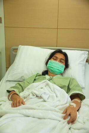 recovery bed: Una donna adulta in un letto di degenza in ospedale di indossare una maschera.