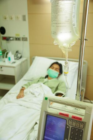 Patient lies in hospital bed with drip equipment in foreground. Focus is on the drip