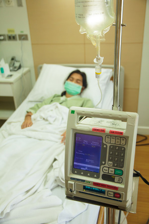 An intravenous IV drip infusion pump next to a patient's bed in a hospital room with selective focus on the foreground.