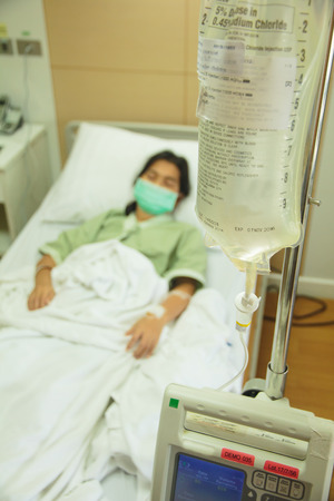 post operative: Patient lies in hospital bed with drip equipment in foreground. Focus is on the drip