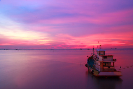 Silhouettes fishing boats at sea in sunset photo