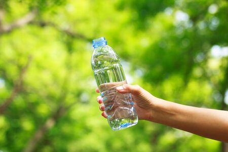Woman hand holding water bottle against green background photo