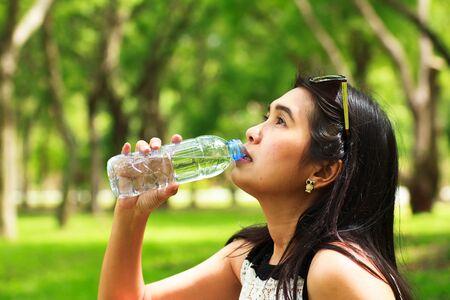 beverage display: Girl is Drinking water at park