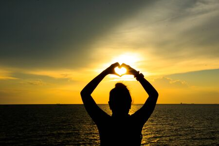 Silhouetted woman forming a heart symbol at golden hour sunset photo