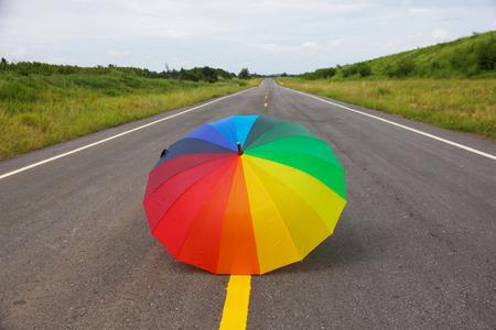 rainbow umbrella: rainbow umbrella on the road Stock Photo