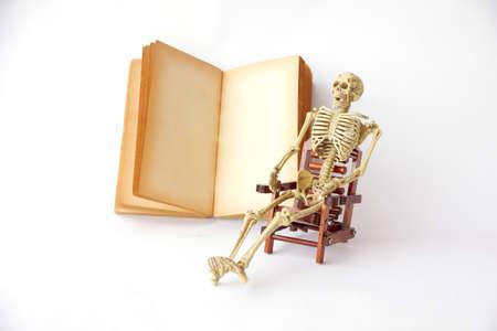 pull toy: Sit esqueleto humano en una silla con libros antiguos sobre fondo blanco Foto de archivo