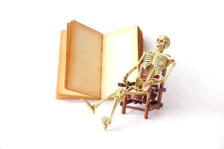 pull toy: Human skeleton Sit on a chair With old books on white background