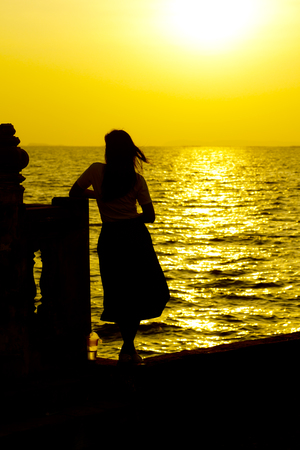 back view of a silhouette of a woman looking forward at sunset on the beach Stok Fotoğraf