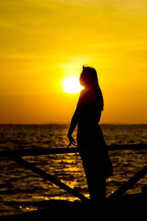 mujer mirando el horizonte: vista trasera de una silueta de una mujer mirando hacia adelante al atardecer en la playa