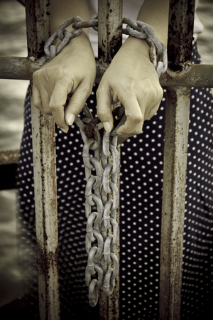 behind: hands tied with rusty chain behind the bars