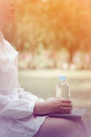salud y deporte: mujer asiática sosteniendo natural del agua en botella de plástico de estilo vintage enfoque suave