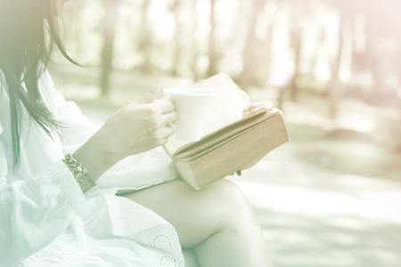 Woman sitting on the park reading a book holding her coffee mug soft focus vintage style