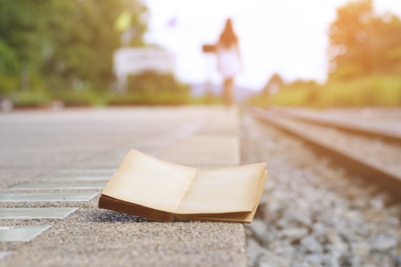 essay: open book on the railroad tracks, with a filter effect