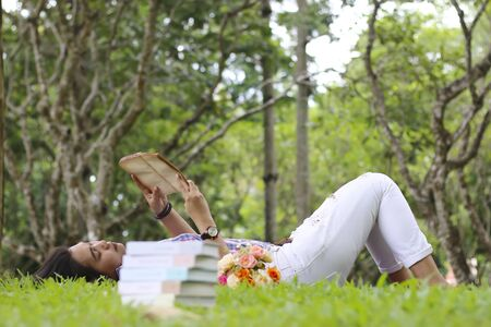novel: Reading woman laying in a park on a sunny summer Sunday