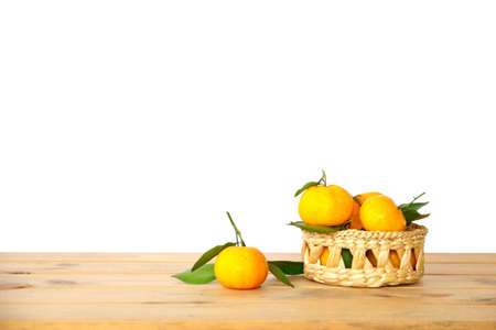 Oranges group freshly picked in a basket and on a brown wooden table Stock Photo