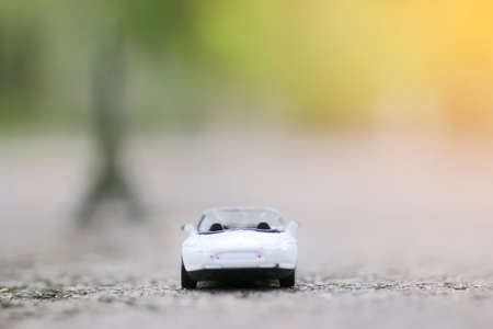 Retro toy car model on the road crossing.Shallow depth of field composition and afternoon scene Stock Photo