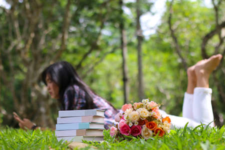 five aged book stack with bottle beside fresh spring green garden with blurred women and sunlight