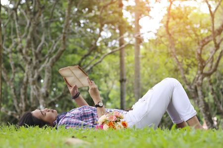 Reading woman laying in a park on a sunny summer Sunday