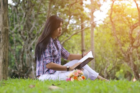 Attractive mature woman reading a book in the park.Moment of leisure. Stock Photo