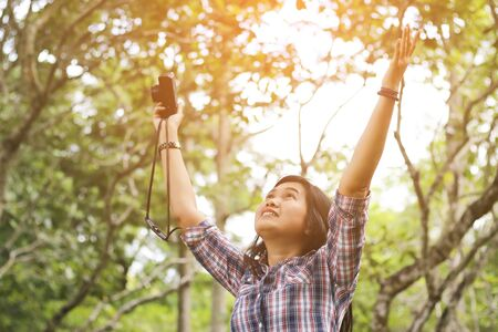 Young woman meditating with open arms standing in fresh spring greenery Stock Photo