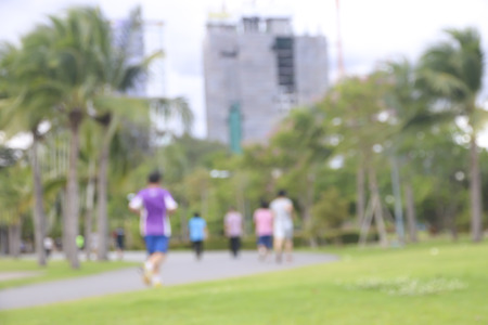 Defocused, blurred motion background of summer activities with energetic people jogging, walking, running and bicycling at green city park. Urban outdoor workout and sport. Healthy lifestyle concept.