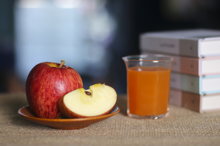 Glasses of juice, apples on wooden table Stock Photo