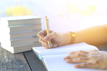addressing: Woman right hand writing journal on small notebook at outdoor area with morning scene