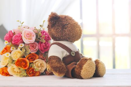 Teddy bear sitting on window with beautiful Faked flowers bouquet.