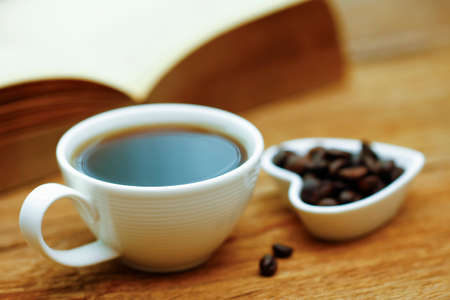 Coffee cup with book on wooden table with blur green nature background - soft focus