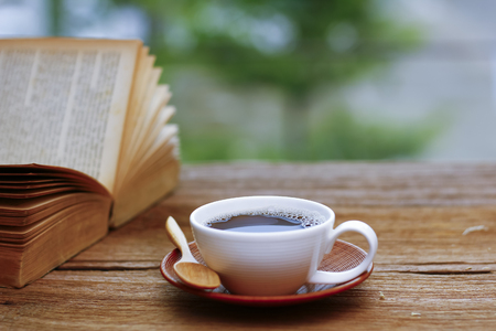 decaf: Coffee cup with book on wooden table with blur green nature background - soft focus