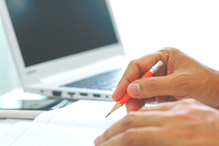 closeup of young man hand writes a pen in a notebook (computer in background)