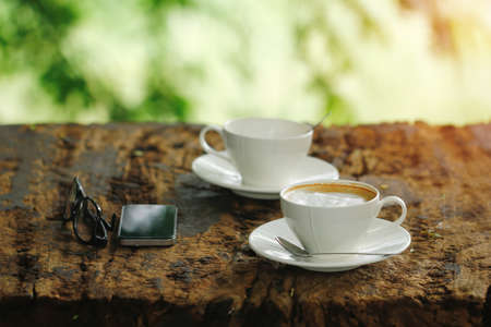 Cappuccino coffee cup on wooden table with mobile phone and glasses