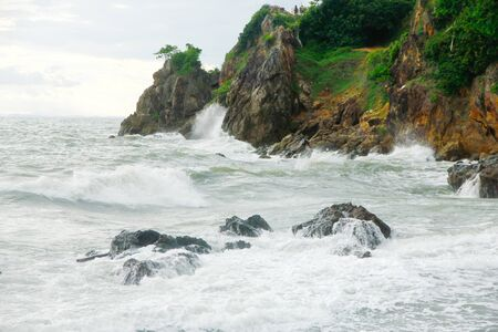 seawater: powerful ocean wave crashes against a rocky reef sending seawater spray into the air