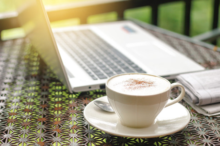 white cups of Cappuccino coffee with newspaper ,laptop or notebook  on vintage table