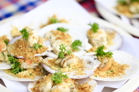 baked scallops with cheese topping fried garlic and boiled vegetable on plate