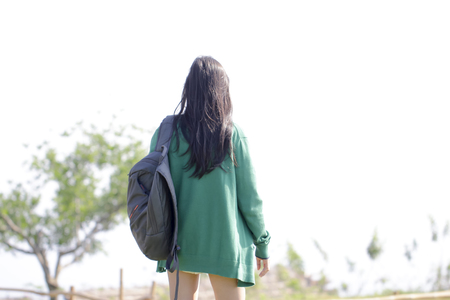 Back view of woman with black long perm hair in green Jacket, standing alone on fell and looking forward