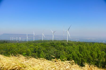 Wind turbine renewable energy source summer landscape with clear blue sky and field in the foreground Archivio Fotografico - 92432573