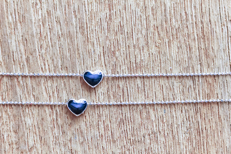 Black diamond heart shape locket pendant with necklace on wooden background