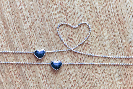 Black diamond heart shape locket pendant with necklace on wooden background