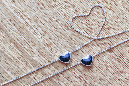 Black diamond heart shape locket pendant with necklace on wooden background Reklamní fotografie - 93168045