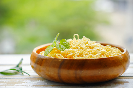 Noodles on Wooden bowl on Table with green background.