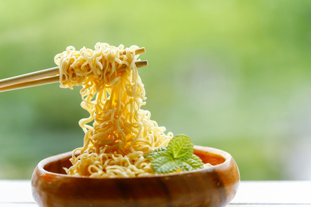 Instant Noodles Put on Wooden Table on green background.