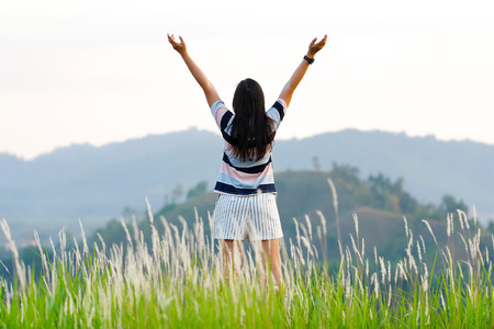 Portrait of beautiful Asian woman trekking on top of a hill looking at the environment. Holding hands up in the air