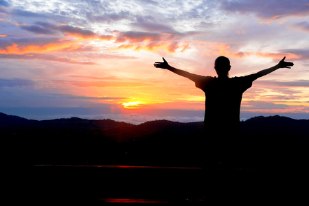 silhouette of a figure of young girl raising her hands to the sky after physical training, a woman enjoying the sunset, concept health Stock Photo