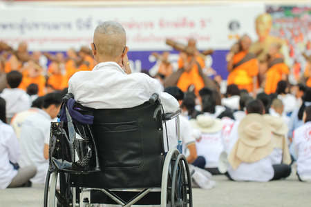 Elderly people ride wheelchair to pay homage to bless.