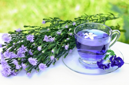 teacup: Violet tea and blossoms with green background