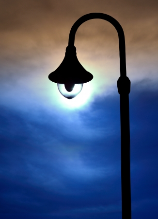 silhouette street lamps on evening sky photo