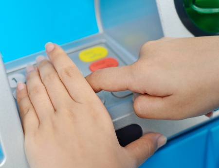 pin entry: Human hand enter atm banking cash machine pin code